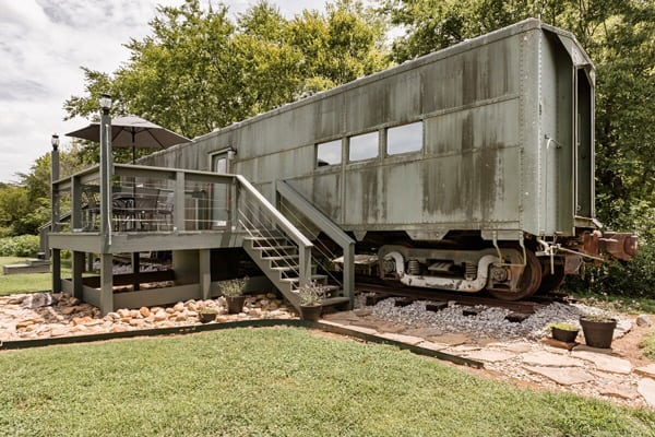 Converted WWII glamping Train Car with Patio outside view with patio and silver train car