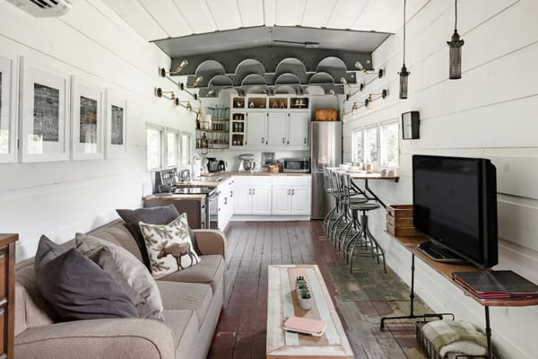 Converted WWII glamping Train Car with Patio inside view with tv, couch, kitchen and wood floors and white walls