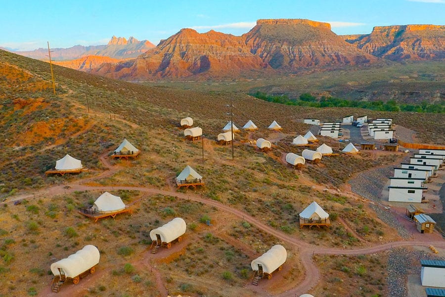 Wildflower Glamping Resort Zion view from above showing covered wagons, bell tents and tiny homes spread out with Zion landscape in the background