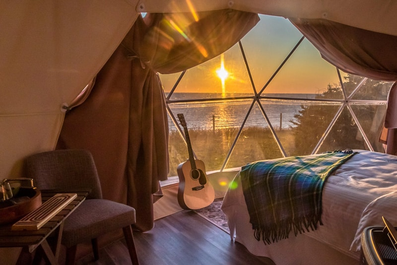 Archer's Edge view from inside with bed, guitar at window with view of the ocean