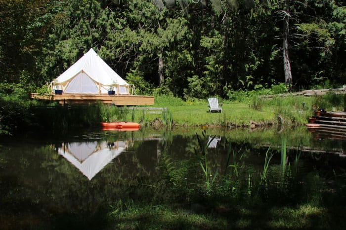 Glamping by the Pond view of a pond with the bell tent in the background next to pond and a chair on grass
