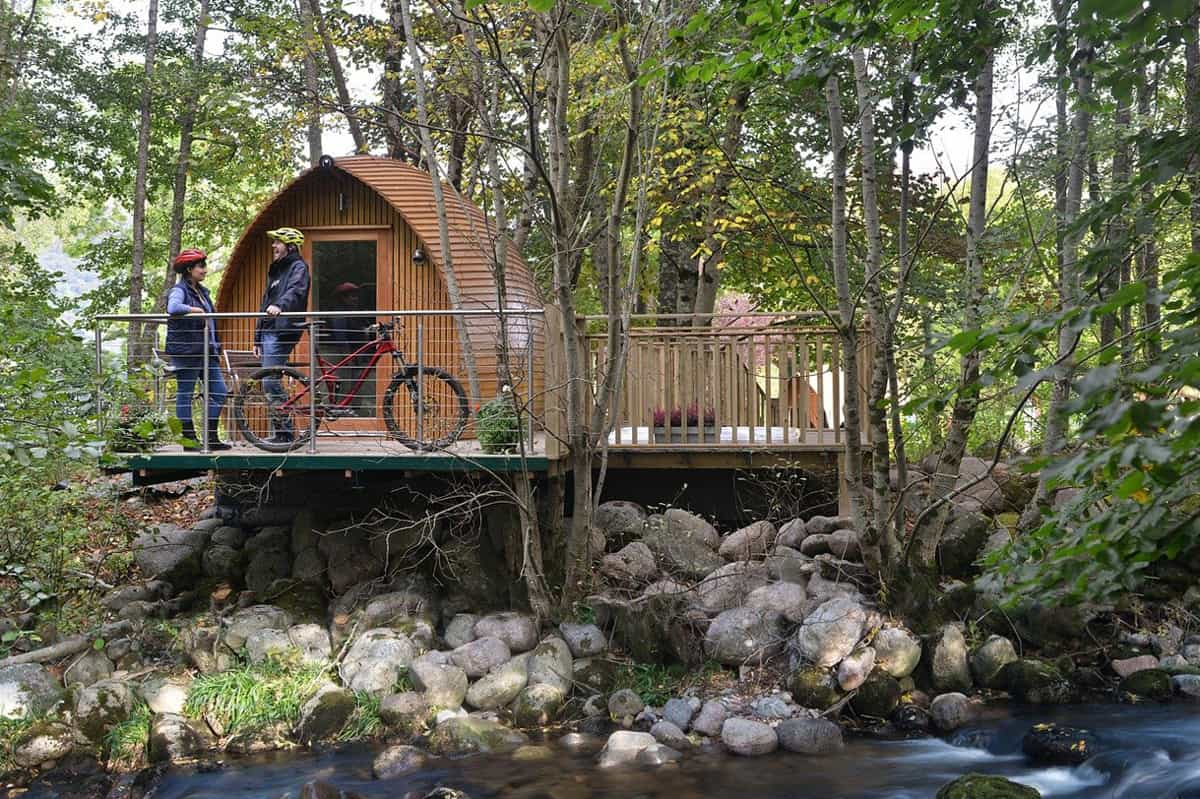 All About Pod Glamping featured image glamping pod with deck above a creek with cyclists on the deck