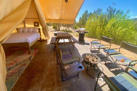 view from east zion glamping tent deck with door open and bed inside and chairs, picnic table, bbq and firepit on the deck