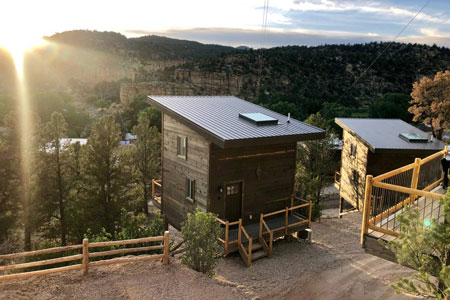view of two east zion glamping treehouses at sunset on a hill side