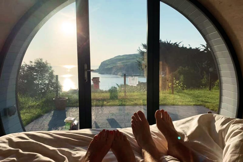 Glenarm Castle Pod Glamping view from the pod bed through the window with feet on bed and view of the coast