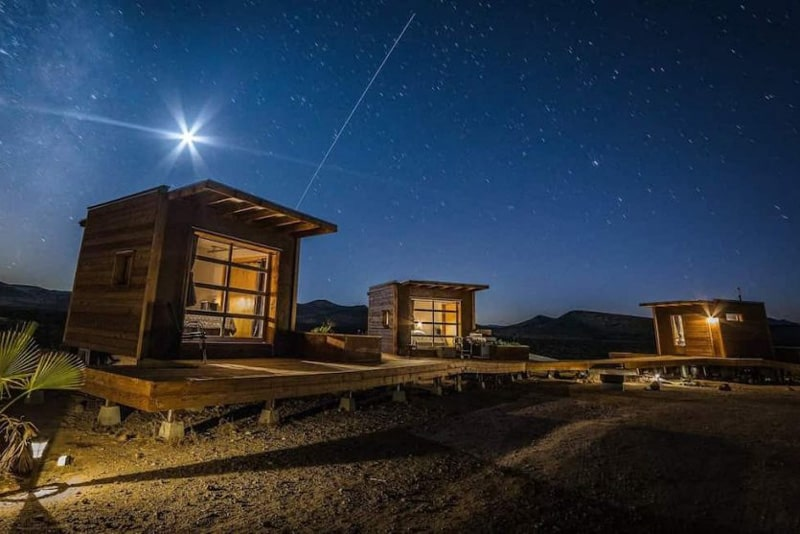 Mojave Desert Eco-Pods view of the pods and bathroom at night with wooden walkway between them