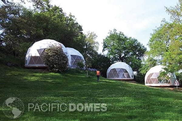 pacific domes glamping domes view of the domes on a grassy hill with 1 person
