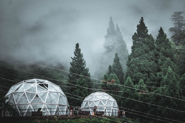 white glamping dome pods  in mountains with trees and fog
