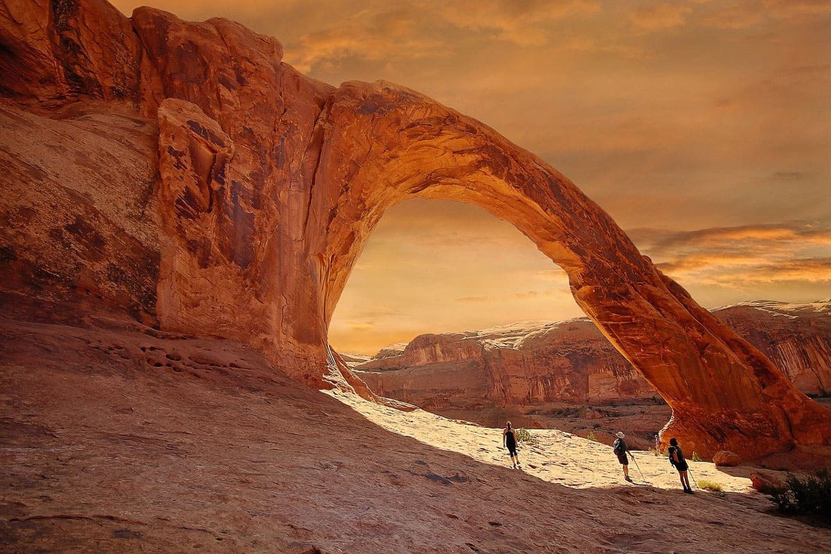 Utah glamping in moab view of an arch with hikers looking at it during sunset