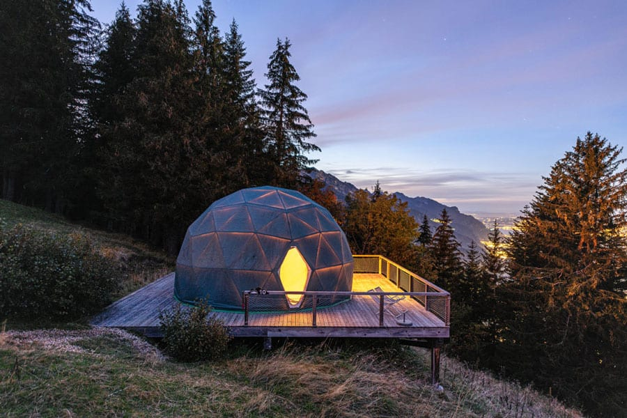 WhitePod Glamping Domes view at sunset with mountains and trees and geodesic dome with deck